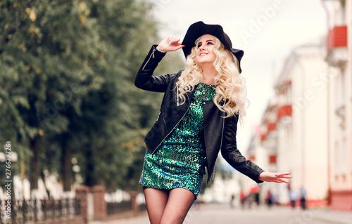 Photographie beautiful blonde girl in a brilliant dress and leather jacket