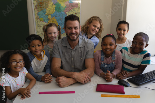 Happy male teacher and schoolkids looking at camera in classroom