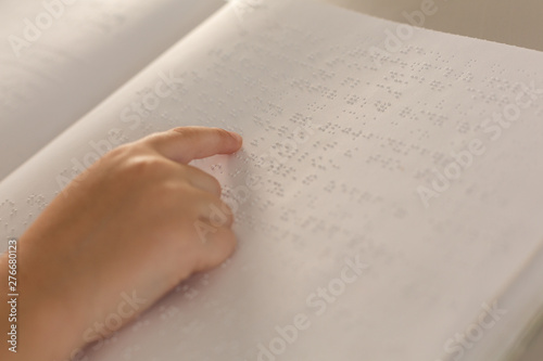 Blind boy hand reading a braille book in classroom