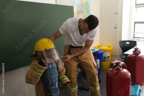 Male firefighter help to wearing fire uniform to schoolgirl in classroom