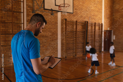 Basketball coach writing on clipboard at basketball court in school