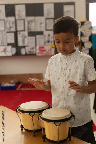 Schoolboy playing bongo in a classroom