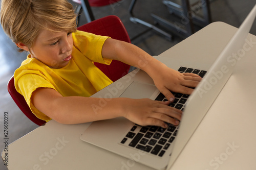 Boy using laptop at desk in a classroom