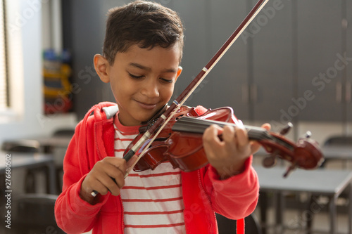 Smiling schoolboy with eyes closed playing violin in classroom