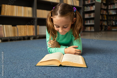 Schoolgirl lying on floor and reading a book in library