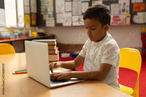 Schoolboy using laptop at table in a classroom