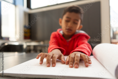 Blind schoolboy hands reading a braille book at desk in a classroom