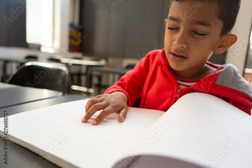 Blind schoolboy reading a braille book at desk in a classroom