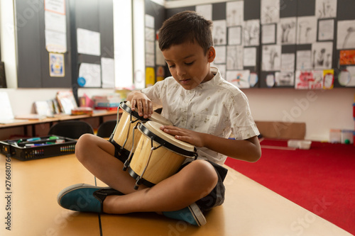 Schoolboy sitting on desk and playing bongo in a classroom