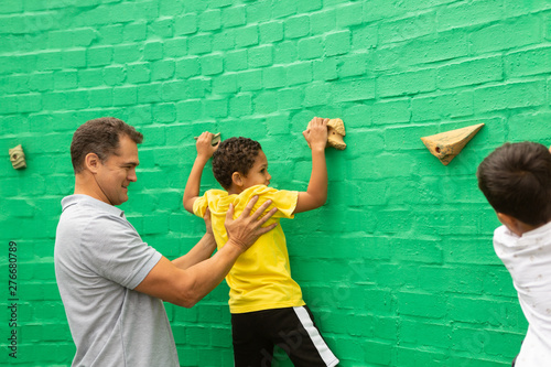 Male teacher assisting a schoolboy to climb artificial wall
