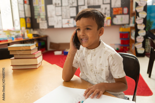 Happy schoolboy talking on mobile phone at desk in a classroom