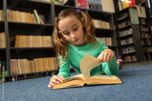 Schoolgirl lying on floor and turning a page in a book in library