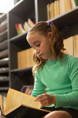 Schoolgirl sitting on floor and reading a book in library