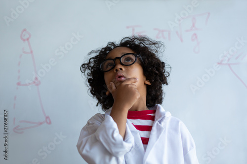 Mixed-race Schoolboy in chemistry coat standing in the laboratory
