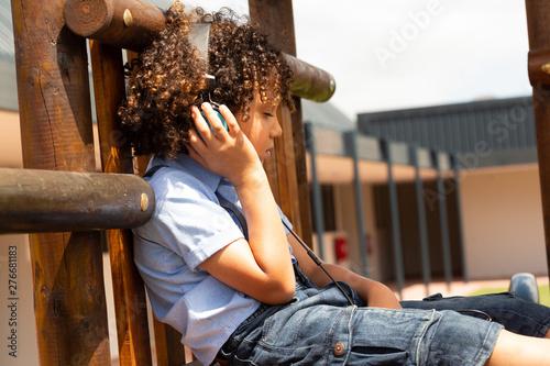 Schoolgirl listening music on headphones in the school playground