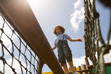 Schoolgirl walking on net bridge in the school playground