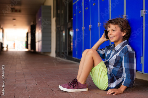 Schoolboy talking on mobile phone while sitting in the corridor