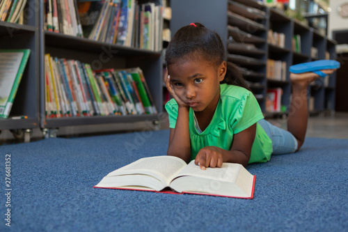 Schoolgirl reading a book in the library