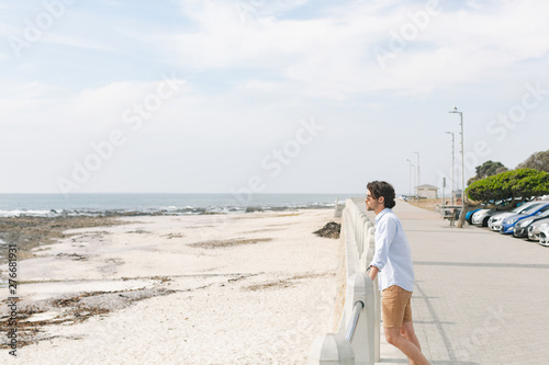 Caucasian man standing near sea side at promenade on a sunny day