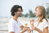 Caucasian couple standing at promenade while having ice cream cone