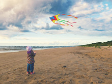 Little Girl Flying A Kite On The Beach At Sunset