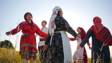 People In Traditional Russian Clothes Performing A Round Dance On The Field