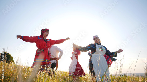 Vászonkép Happy people in traditional russian clothes performing a round dance on the fiel