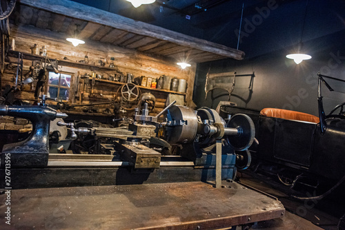 Obraz Workshop scene. Old tools hanging on wall in workshop, Tool shelf against a table and wall, vintage garage style - fototapety do salonu