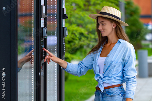 Obraz Young woman in hat using vending machine on the street during a walk around the city for buying soda and sweets - fototapety do salonu