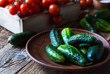 Plate Of Freshly Picked Organic Cucumbers, Cherry Tomatoes On Rustic  Table