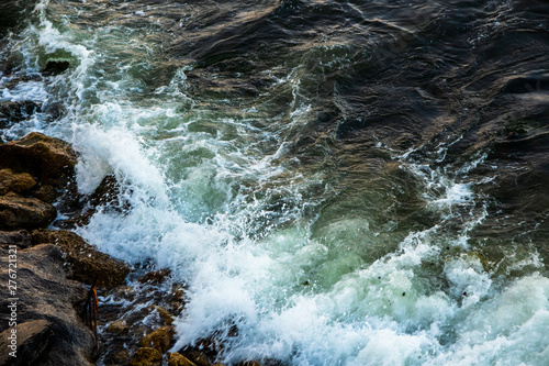 Foto auf Leinwand Forest river Waves hitting to the rock on a sea coast at evening