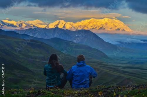 Photo  Sunrise view of Mount Denali - mt Mckinley peak with alpenglow during golden hour with two persons from Stony Dome overlook
