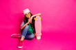 Leinwandbild Motiv Full length body size photo beautiful little she her curly lady sit floor risky hobby long board hands arms modern look wear yellow sun specs hat casual jeans denim jacket isolated pink background