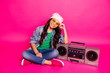 Leinwandbild Motiv Full length body size photo beautiful little she her curly lady sit near old-fashioned tape sound audio recorder legs crossed wear yellow specs hat casual jeans denim jacket isolated pink background
