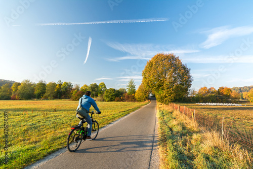 Obraz na plátně  Cyclist on a bike lane in rural landscape in the fall