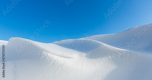 Snow dunes caused by drifting snow and the wind in winter with bright sunlight Canvas-taulu