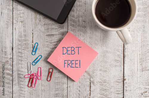 Fototapety, obrazy: Handwriting text writing Debt Free. Conceptual photo does not owning any money to any individual or companies Stationary placed next to a cup of black coffee above the wooden table