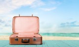 Fototapeta Coffie - Retro suitcase with travel objects  on sea background