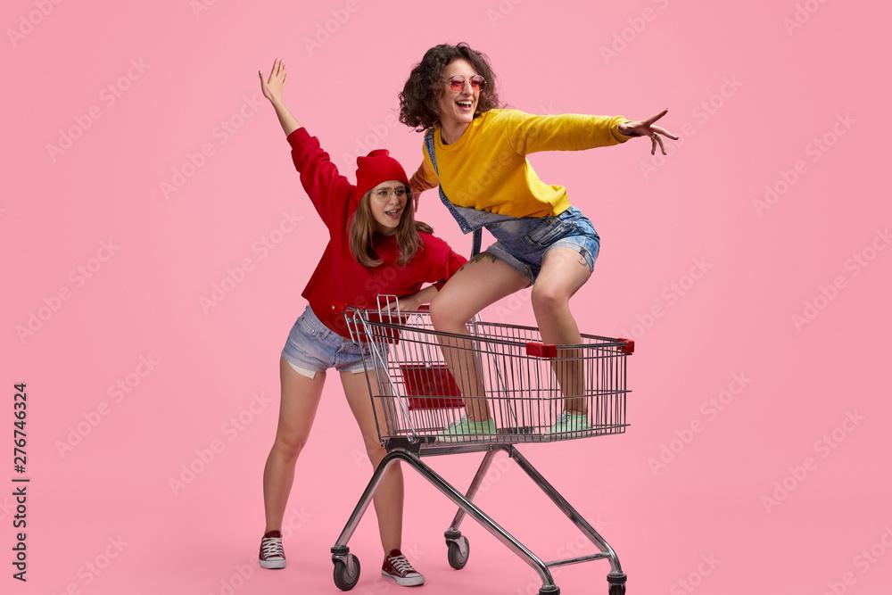 Fototapeta Best friends riding shopping cart