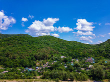 The Village At The Foot Of The Mountain, Covered With Green Vegetation, Against A Blue Sky With White Clouds.