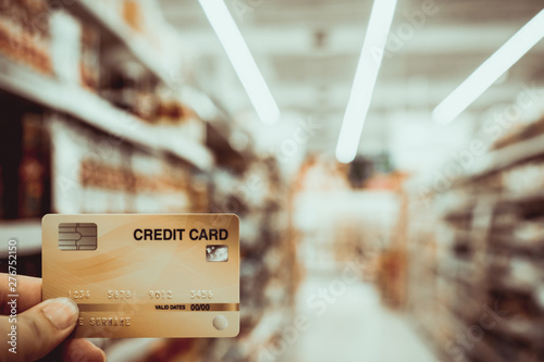 Photo Stands Coffee beans Hand holding credit card with blur supermarket, shopping and retail concept