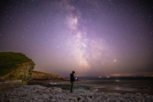 Stargazing Photographer With Camera And Tripod On Beach At Night Below Milky Way Starscape