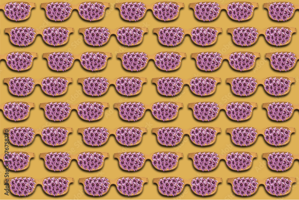Yellow sunglasses with purple flowers on a yellow creative background. Summer concept.