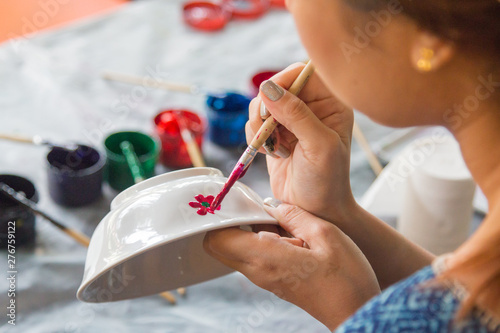 Fotografia, Obraz Close-up hands holding a bowl during painting in Lampang province, Thailand
