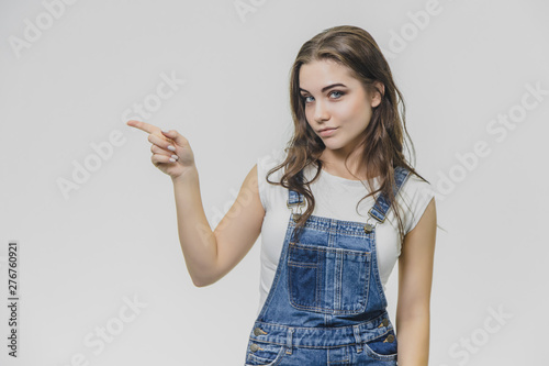 A young attractive student girl shows her forefinger aside. Tries to concentrate and looks into the camera. Dressed in white t-shirt and denim overalls. Isolated over white background.