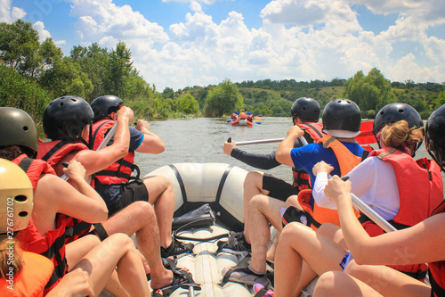 Rafting team , summer extreme water sport. Group of people in a rafting boat, beautiful adrenaline ride down the River. Back view. POV