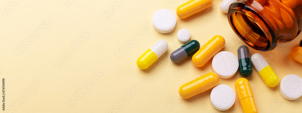 Fototapeta Multicolor tablets and pills capsules from glass bottle on yellow background Health care Close-up Horizontal banner Copy space