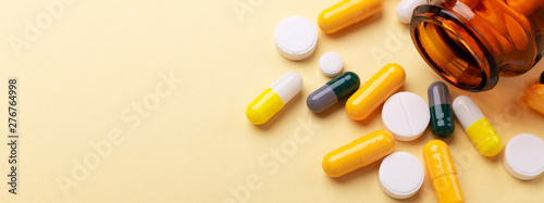 Multicolor tablets and pills capsules from glass bottle on yellow background Hea Canvas Print