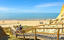 A Couple Walking Down The Wooden Walkway Towards The Asperillo Beach, Very Close To The Famous Doñana National Park In The Province Of Huelva, Andalusia, Spain