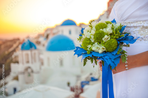 Foto auf Gartenposter Santorini Bride holds wedding bouquet in white and green colors and blue decor against the backdrop of the sunset over Santorini, Greece